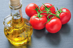 Bottle of olive oil with herbs and red tomatoes Stock Photography
