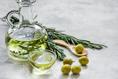 Bottle with olive oil and herbs on stone background mockup. Glass bottle with olive oil and herbs on stone table background mockup Stock Image