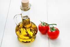 Bottle of olive oil with herbs and two red tomatoes Stock Photo