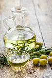 Bottle with olive oil and herbs on wooden background. Glass bottle with olive oil and herbs on wooden table background Royalty Free Stock Image