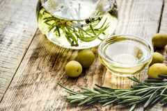 Bottle with olive oil and herbs on wooden background Royalty Free Stock Photo