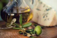 Bottle of olive oil on old wooden table and cheese Stock Image