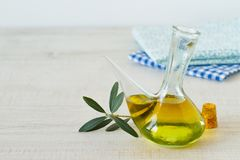 Bottle of olive oil with olive branch. On a rustic wooden table Royalty Free Stock Photography