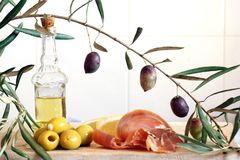 A bottle with olive oil, an olive branch and a light breakfast from stuffed olives and a jamon. A bottle with olive oil, an olive branch and a light breakfast Royalty Free Stock Photography