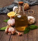 Bottle with olive oil. Olive oil with  green basil and  garlic on a table Royalty Free Stock Image