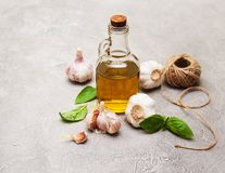 Bottle with olive oil. Olive oil with  green basil and  garlic on a table Royalty Free Stock Photo