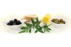 Bottle of olive oil. With olives, crispy baguette and olive branch on a bright background Stock Photos