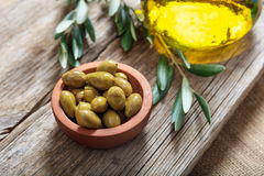 Bottle of olive oil and olives on a table Stock Photo