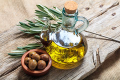 Bottle of olive oil and olives on a table Stock Photography