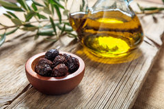 Bottle of olive oil and olives on a table. Bottle of olive oil and olives on a wooden table Royalty Free Stock Photography