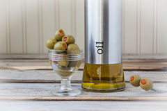 Bottle of olive oil with olives on wood background Stock Photos