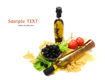 A bottle of olive oil with pasta and black olives. Isolated on a white background Royalty Free Stock Image