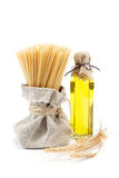 A bottle of olive oil, pasta and ears of wheat. Stock Photo