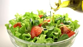 Bottle of olive oil pouring over mixed salad. stock footage