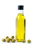 Bottle of olive oil and some olives. Isolated on the white background Stock Photos