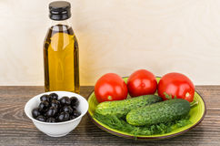 Bottle of olive oil, tomatoes, cucumbers and dill in plate. Bowl with olives Royalty Free Stock Photography