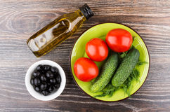 Bottle of olive oil, tomatoes, cucumbers and dill Stock Photos