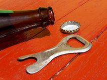 Bottle and opener on the table Royalty Free Stock Images