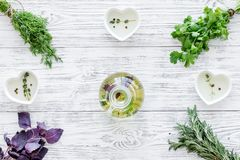 Bottle with organic oil with herbs ingredients on light wooden background top view. Bottle with organic oil with herbs ingredients on light wooden kitchen table Royalty Free Stock Image