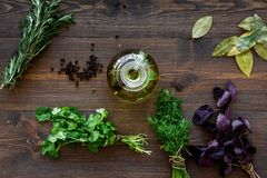 Bottle with organic oil with herbs ingredients on wooden background top view. Bottle with organic oil with herbs ingredients on wooden kitchen table background Royalty Free Stock Images