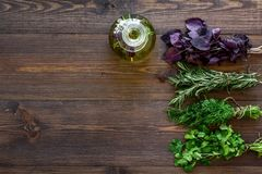 Bottle with organic oil with herbs ingredients on wooden background top view mockup. Bottle with organic oil with herbs ingredients on wooden kitchen table Royalty Free Stock Photo