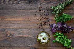 Bottle with organic oil with herbs ingredients on wooden background top view mockup Stock Photos