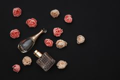 Bottle Perfume and Fake Roses on dark Black Background with copy Space Text flat Lay Top view Royalty Free Stock Photo