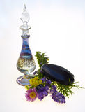 Bottle of perfume with flowers and stone. A perfume bottle with some flowers and a stone used for hot stone massage Royalty Free Stock Photography