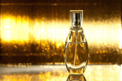 Bottle of perfume on golden background Stock Photos