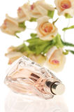 Bottle of perfume with roses Stock Images