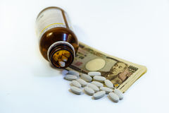 Bottle of pills over bills Stock Photo