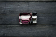Bottle of pink perfume on dark gray wooden table Royalty Free Stock Images
