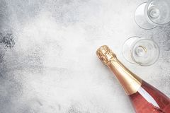 Bottle with pink sparkling wine or rose champagne and glasses, gray background with place for text, holiday or date concept, flat. Lay, top view stock image