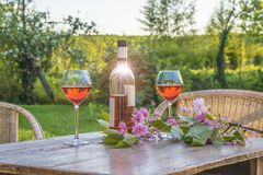 Bottle of pink wine and two wineglasses on old wooden table outd. Oors Royalty Free Stock Photos