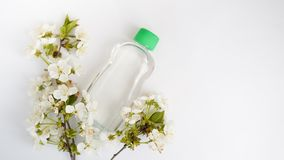 Bottle placed for mock up  on white background and flowers. The concept of natural beauty products stock image