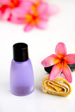 Bottle, plumeria flower, yellow towel and stones Royalty Free Stock Image