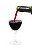 A bottle pouring red wine into a clear glass Stock Photos