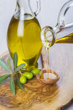 Bottle pouring virgin extra olive oil on a spoon Stock Photography