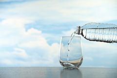 A bottle pouring the water into a glass Royalty Free Stock Image
