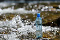 Bottle pure water on the stones in the river. Stock Images
