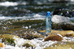 Bottle pure water on the stones in the river. Royalty Free Stock Photography