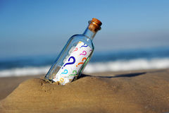Bottle with questions of all colors on the beach stock photography