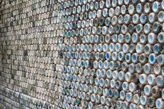Concrete wall made of recycled plastic bottles. Bottle recycling: plastic bottles which have been set in concrete to form a bottle wall Royalty Free Stock Photo
