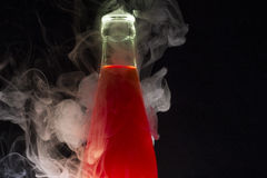 Bottle with red liquid surrounded with smoke. Glass bottle with red liquid surrounded with smoke Royalty Free Stock Image