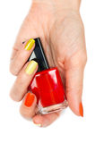 A bottle of red nail polish in a female hand Stock Images