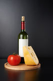 Bottle of red vine with cheese and tomato. On black background Stock Images