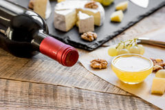 Bottle of red wine, appetizers and corkscrew on wooden background.  Royalty Free Stock Photos