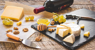 Bottle of red wine, appetizers and corkscrew on wooden background.  Stock Photography