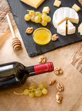 Bottle of red wine, appetizers and corkscrew on wooden background.  Stock Images