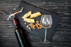 Bottle of red wine, appetizers and corkscrew on wooden background.  Royalty Free Stock Photo